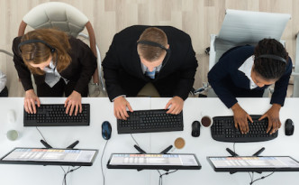 High Angle View Of Call Center Operators Working On Computers In Office